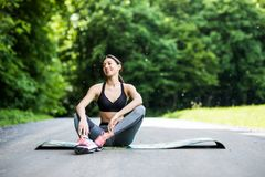 Outdoor workout woman. Fitness woman runner sitting after training outside in park stock image