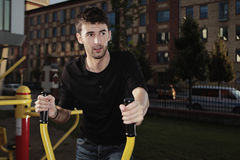 City fitness. Outdoor workout - young man posing on location of open air fitness stock photography