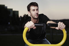 Outdoor evening. Outdoor workout - young man posing on location of open air fitness royalty free stock photography