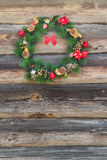 Outdoor X-mas spruce wreath at old log cabin wall background Royalty Free Stock Photography