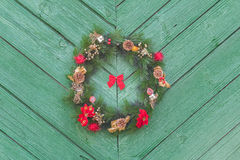 Outdoor X-mas wreath from fir branches at old rustic door background Royalty Free Stock Images