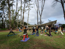 Outdoor Yoga class, led by Kara Miller, does warrior two Stock Image