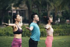 Outdoor yoga practice. Young Vietnamese people enjoying fresh air and yoga practice outdoors Royalty Free Stock Images