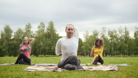 Outdoor yoga training in the park - man and two beautiful fitness models performs the exercises stock video footage