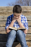 Outdoor.Young boy reading a book in the woods with shallow depth Stock Photo