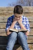 Outdoor.Young chłopiec czyta książkę w drewnach z płytką głębią Zdjęcie Stock