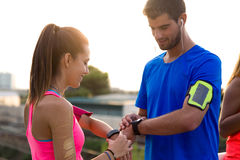 Outdoor young couple using they smartwatch after running. Outdoor portrait of young couple using they smartwatch after running Stock Photo