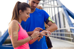 Outdoor young couple using they smartwatch after running. Outdoor portrait of young couple using they smartwatch after running Royalty Free Stock Images