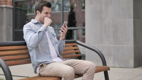 Outdoor young man excited for success on smartphone stock footage