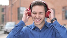 Outdoor Young Man Listening Music on Red Headphones. 4k high quality, 4k high quality stock video