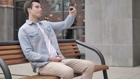 Outdoor young man taking selfie on phone stock footage