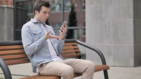 Outdoor young man upset by loss while using smartphone stock video footage