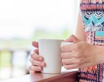 Young woman enjoying a mug of beverage Stock Photos