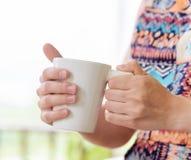 Young woman enjoying a mug of beverage Royalty Free Stock Photography