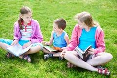 Outdoori de livre de lecture d'enfants d'amis sur l'herbe Images libres de droits