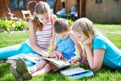 Outdoori de livre de lecture d'enfants d'amis sur l'herbe Photo libre de droits