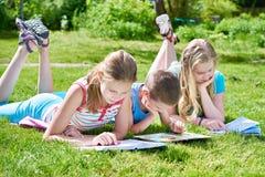 Outdoori de livres de lecture d'enfants d'amis sur l'herbe Image stock