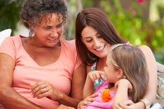 坐Outdoorsï ¿ ½的祖母、母亲和孙女 库存图片