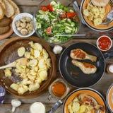 Outdoors концепция еды Аппетитные barbecued ноги цыпленка, обломоки и салат свежих овощей на деревянном столе для пикника, взгляд Стоковое Изображение RF
