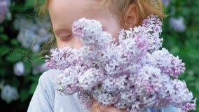 Outdoors маленькой девочки в парке или саде держит цветки сирени r Лето, парк видеоматериал