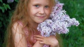 Outdoors маленькой девочки в парке или саде держит цветки сирени r Лето, парк сток-видео