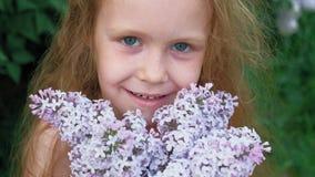 Outdoors маленькой девочки в парке или саде держит цветки сирени r Лето, парк акции видеоматериалы