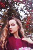 Outdoors портрет моды образа жизни девушки брюнет Нося стильное красное пальто Длинные курчавые светлые волосы Радостная и жизнер стоковое изображение