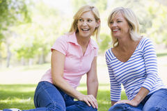 outdoors сидя усмехаться 2 женщины Стоковые Фотографии RF