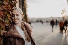 Outdoors фасонируйте белокурую молодую женщину представляя на волшебных листьях осени на предпосылке около здания на улице Стоковое Изображение RF