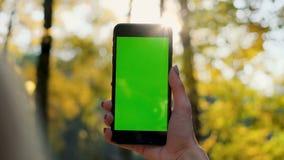 Outdoors экрана зеленого цвета телефона показа девушки, городское Environmen Смартфон удерживания руки женщины с ключом chroma ко акции видеоматериалы