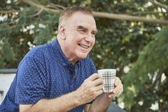 Кофе человека выпивая outdoors стоковое фото