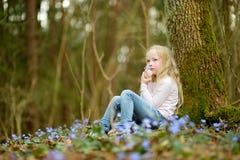Прелестная маленькая девочка комплектуя первые цветки весны в древесинах на красивый солнечный весенний день стоковая фотография