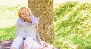 Ноутбук девушки мечтая в парке сидит на траве Мечта об успешном проекте Женщина мечтательная с работой ноутбука outdoors стоковое изображение