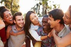 Группа в составе друзья имея потеху совместно Outdoors Стоковое Фото