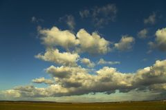 Outdoors. Image of a field and blue sky and clouds Stock Image