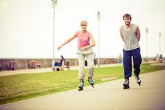 Friends rollerblading together have fun in park. Royalty Free Stock Photos