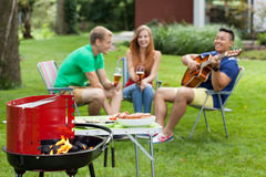 Outdoors barbeque. Group of people having outdoor barbeque at home royalty free stock photography