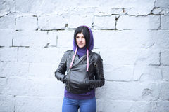 Outdoors beautiful young brunette woman posing in a black leather. Beautiful young sexy brunette girl in a hooded jacket with a brick wall, street style in the Stock Image
