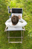 Outdoors. Bird view on man typing on his laptop computer. Bird view on young adult typing on his large laptop computer isolated on green grass. He is smart Stock Image