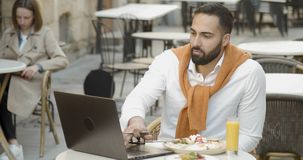 The Outdoors Breakfast. Attractive young bearded businessman has breakfast in outdoors restaurant while working on laptop stock video