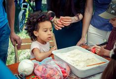Outdoors children activity on charity family festival. Zaporizhia/Ukraine- June 2, 2018: small curious girl, wearing band with funny mouse ears, on flour and royalty free stock photo