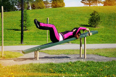 Outdoors exercise. Women doing exercise on the sports device, in the park. Let's be healthy and full of energy Royalty Free Stock Photo