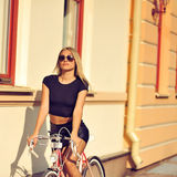 Outdoors fashion portrait of a beautiful blonde model with bike Stock Image