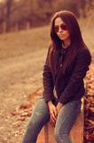 Outdoors fashion portrait of young brunette woman in sunglasses. Stock Photos