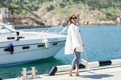 Fashion whilte outfit of trendy beautiful laughing woman in sunglasses posing on the white yacht background stock image
