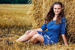 Outdoors fasonuje portret młoda kobieta siedzi blisko haystack w błękit sukni fotografia royalty free
