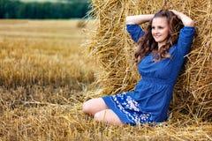 Outdoors fasonuje portret młoda kobieta siedzi blisko haystack w błękit sukni obrazy royalty free