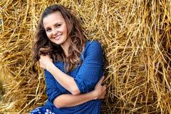 Outdoors fasonuje portret młoda kobieta siedzi blisko haystack w błękit sukni zdjęcie royalty free