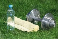 Outdoors fitness activity items in grass. Bottle of water, towel and dumbbell Stock Images