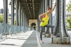Woman jogger relaxing after workout on Pont de Bir-Hakeim bridge. Outdoors fitness in Paris. Full length portrait of young woman jogger relaxing after workout on royalty free stock image